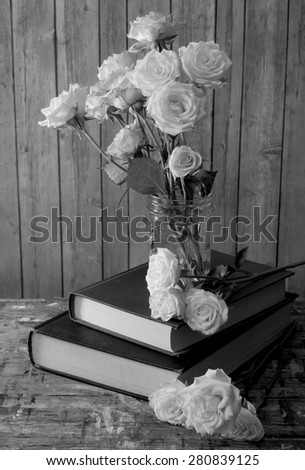 Black and white image of tired, white miniature tea roses in a mason jar on a stack of dusty books. The table top is old wood with many paint stains. Background is rustic wood. Side lighting from left - stock photo