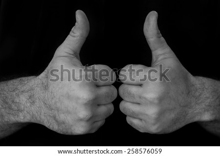 Black and white image of two hands giving a thumbs up - stock photo