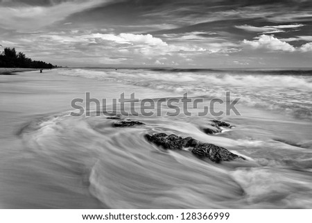 Black and white image of waves motion at the beach - stock photo