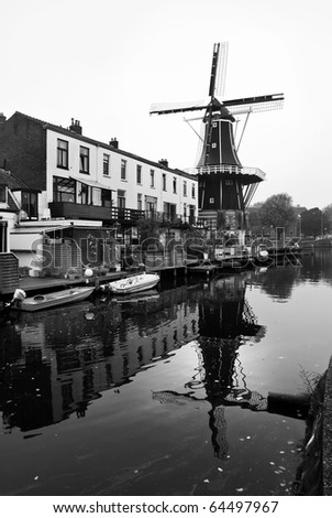 Black and white image of windmill and canal in the Netherlands - stock photo