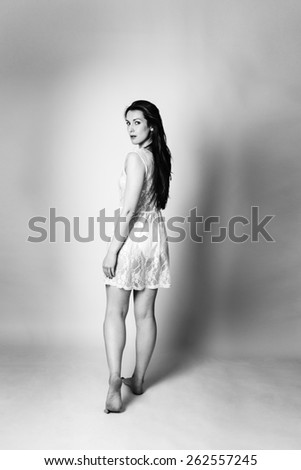 black and white image of woman shot in the studio standing and walking away looking back round at the camera wearing a lace dress - stock photo