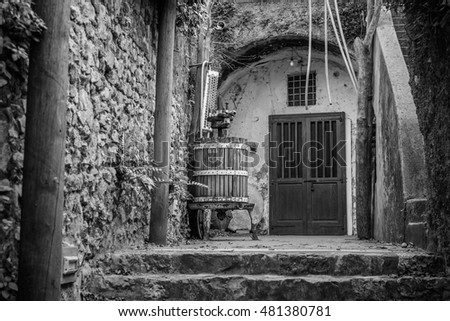 Black and white image with wine press and closed doors. Old Italian wooden wine press for pressing grapes to produce wine.
