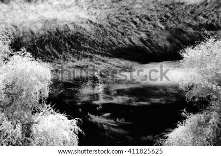 Black and white infrared  image with trees in the foreground against a dramatic sky filled with clouds - stock photo