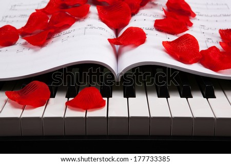 black and white keys of the piano closeup and musical book with rose petals
