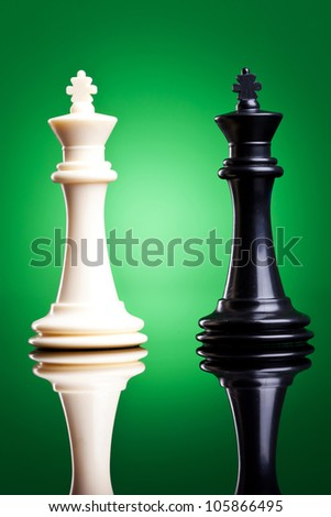 black and white kings on green background with reflection - chess pieces