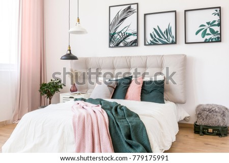 Black and white lamp above bed with pink and green blanket against a wall with gallery