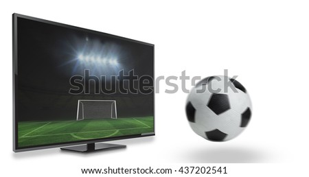 Black and white leather football against football pitch and goal under spotlights