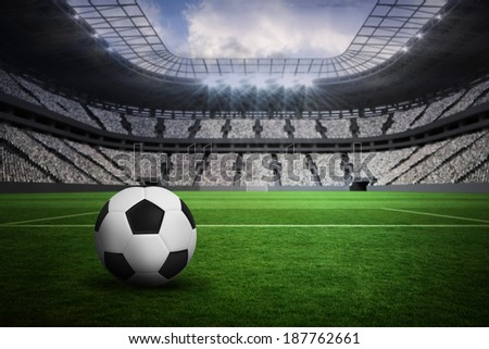 Black and white leather football in a vast football stadium with fans in white - stock photo