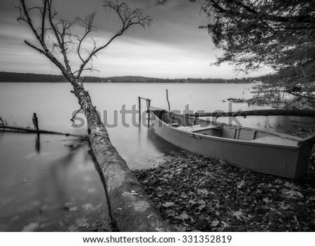 Black and white long exposure landscape of lake shore with moored boats. Lake Krzywe in Olsztyn, Poland. - stock photo