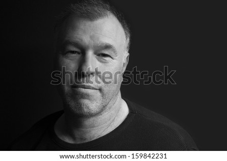 Black and white low key portrait of middle-aged man - stock photo