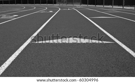 Black and white low point of view of cross country track showing lanes and markers. - stock photo