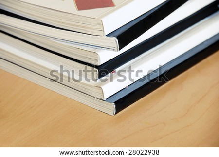 black and white magazines  pile closeup on wooden desk - stock photo