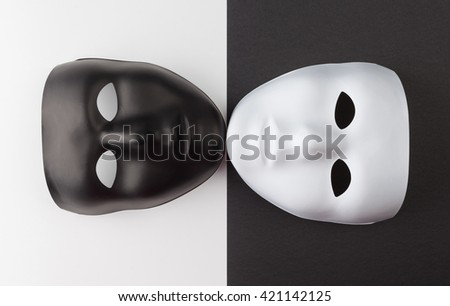 Black and white masks touching chins on contrasting backgrounds, Personality change theatrical concept - stock photo