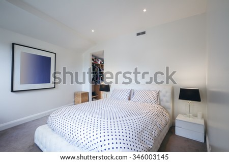 Black and white master bedroom with walk in wardrobe in Australian home - stock photo