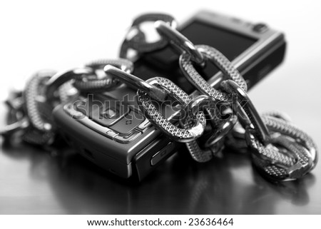 Black and white metaphor of being slave in chains to the mobile phone - stock photo