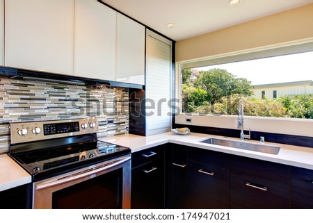 Black and white modern kitchen room with multi-color backsplash - stock photo