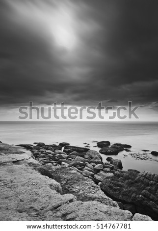 Black and white monochrome dramatic landscape Portland Bill Weymouth Dorset UK coast sea cliff rocks clouds