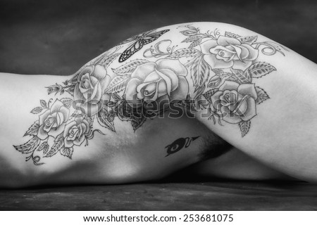 Black and white naked woman body scape with big tatoo over black background