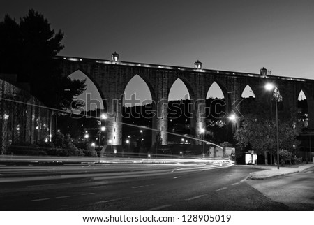 black and white night shoot of the historic aqueduct in the city of Lisbon built in 18th century, Portugal - stock photo