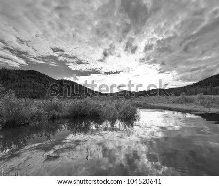 Black and white of a lake inlet at sunset - stock photo