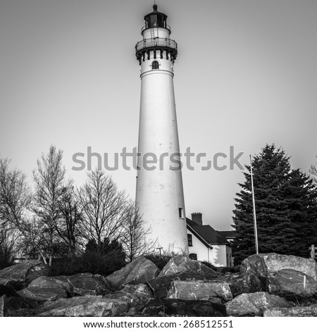 Black and White of a lighthouse with rocky shoreline on Lake Michigan in Wisconsin - stock photo
