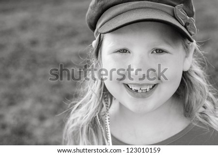 Black and white of a little girl with a large natural smile outside - stock photo