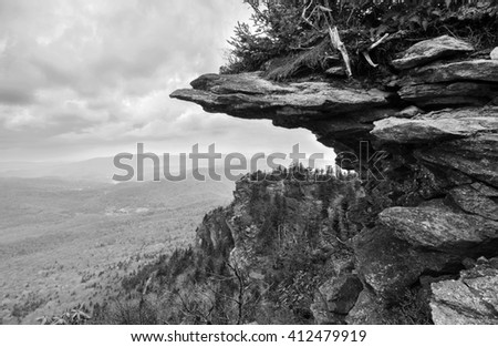 Black and white of a rocky weathered cliff jutting out from an Appalachian peak at Grandfather Mountain - stock photo