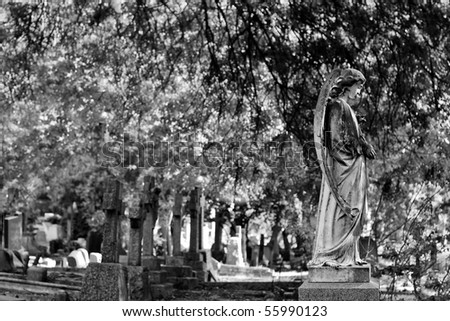 black and white of a statue in a graveyard/cemetery - stock photo
