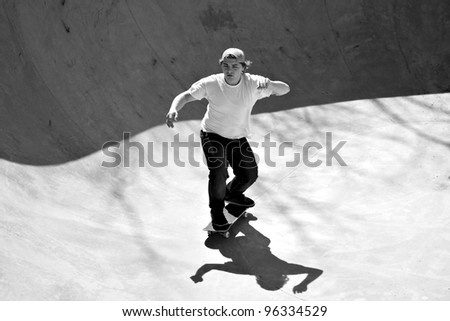 Black and white of a young skateboarder skating in the bottom of the bowl at a concrete skate park.