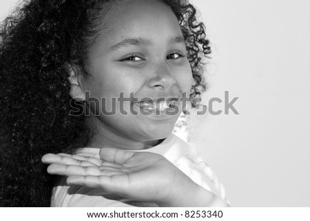 Black and white of child holding hand up with big smile. - stock photo
