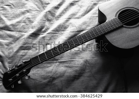 Black and white of classic guitar on bed