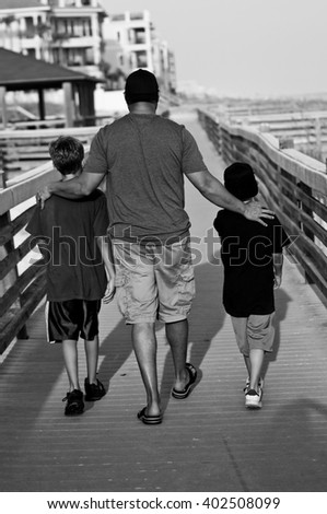 Black and white of Dad walking with his two boys with arms around their shoulders. - stock photo