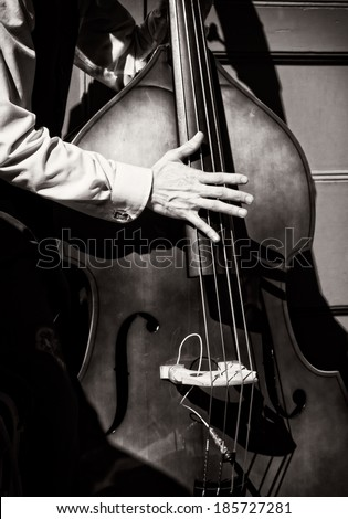 Black and white of musician playing bass fiddle.