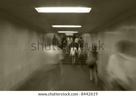 Black and white of people walking in a tunnel with motion blur. - stock photo