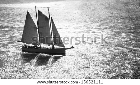 Black and white of sailboat sailing through suns reflection. - stock photo