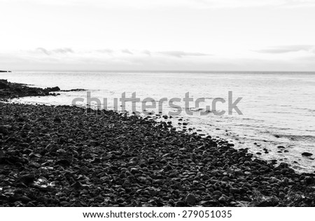 Black and white of stone beach near Dragon Head Rock or Yongduam Rock in Jeju Island, South Korea - stock photo