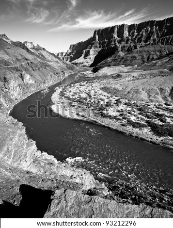 Black and White of the winding Colorado River through the Grand Canyon from up on top of a large mesa looking down at the river - stock photo