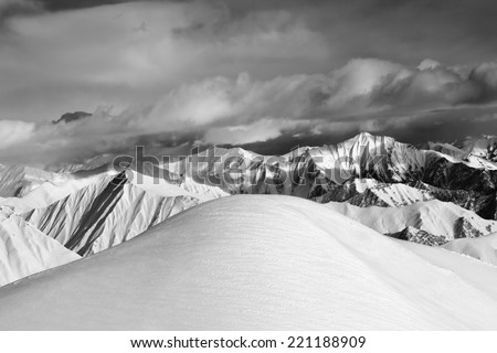 Black and white  off-piste snowy slope and cloudy mountains. Caucasus Mountains, Georgia, ski resort Gudauri. - stock photo
