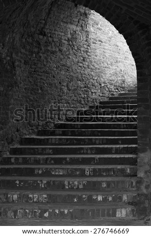 Black and white old rustic gothic brick stairway tunnel at Petrovaradin, Novi Sad, Serbia. - stock photo