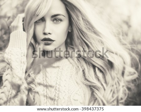 Black and white outdoor fashion photo of young beautiful lady
