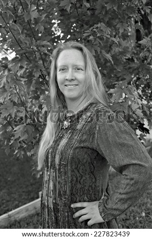 Black and white outdoor portrait of a natural looking blond woman. - stock photo