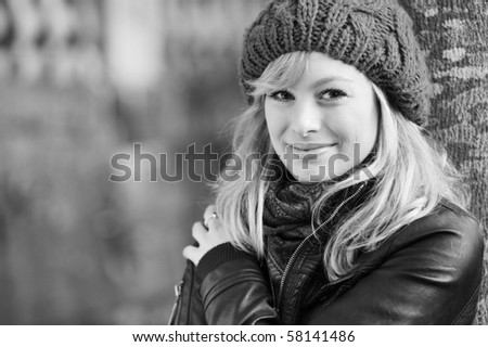 Black And White Outdoor Portrait Of Young Woman Leaning Against A Tree - stock photo