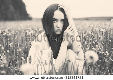 Black and white outdoors art photo of beautiful lady in dandelions field - stock photo