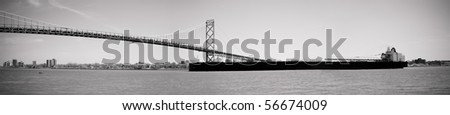 Black and white panoramic image of a large cargo ship passing under the Ambassador Bridge connecting Detroit, Michigan and Windsor, Ontario over the Detroit River (part of the St Lawrence Seaway).