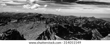 Black and White Panoramic Scenic View of Expansive Alpine Mountain Range with Dramatic Clouds - stock photo
