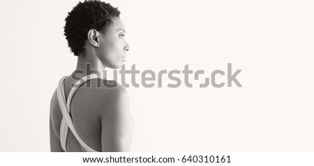 Black and white panoramic view of elegant african american woman wearing smart party dress, serene against white wall, interior. Fashionable black female dressed up showing back, lifestyle model.