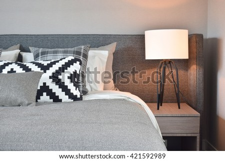 Black and white pattern pillows with gray blanket and white shade bedside table lamp - stock photo