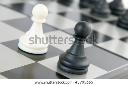 Black and white pawns on a board - stock photo