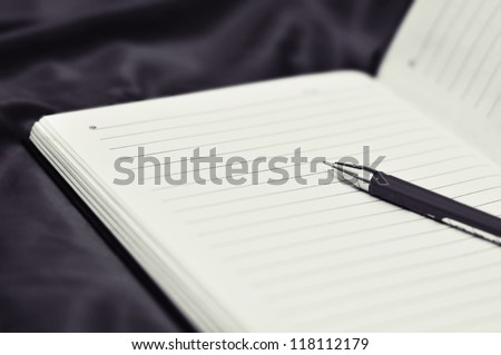 Black and white pen on diary page - stock photo