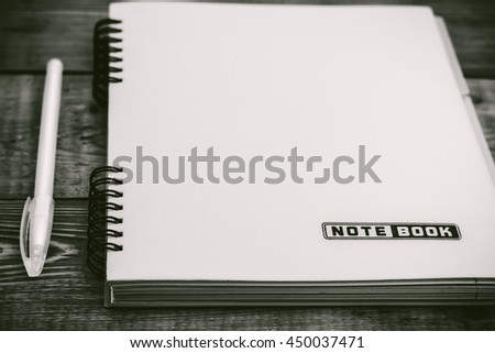 Black and White  pen on the closed notebook lying on a wooden table - stock photo